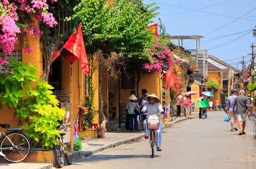 Femme à vélo dans les rues d'Hoian, Vietnam
